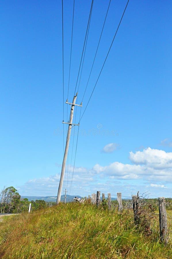 Viejos posts de madera de la electricidad al lado de la calle en el campo foto de archivo libre de regalías