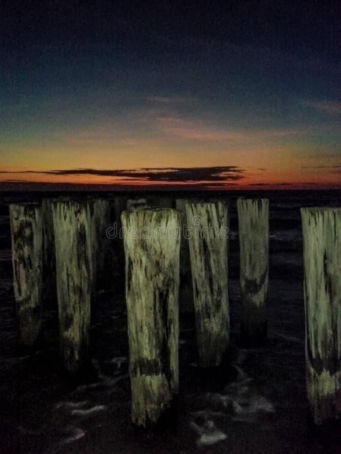 Viejos posts del embarcadero contra un cielo oscuro dramático fotografía de archivo libre de regalías
