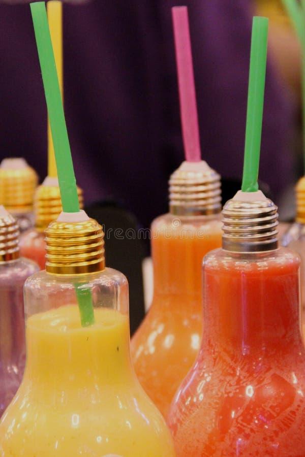 Viel kleine Flasche in Form einer Glühlampe, voll von den hellen farbigen nützlichen Obst- und gemüsesäften mit Trinkhalm auf lizenzfreie stockbilder