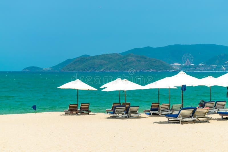 Viel von weißen Sonnenschirmen auf Strand mit Ruhesesseln und Inselhintergrund stockbild