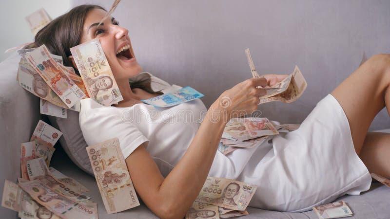 Viele Banknoten fliegen in die Luftunkosten in der Zeitlupe Ein M?dchen liegt und viele Geldf?lle auf sie gl?ckliche Frau freut s stockfoto