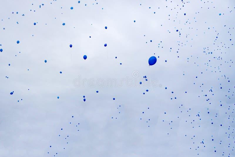 Viele blauen Ballone fliegen in den Himmel stockbild