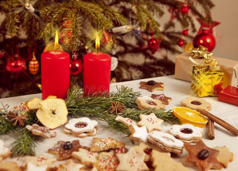 Viele bunten Kekse und Kerzen vor Weihnachtsbaum lizenzfreie stockfotografie