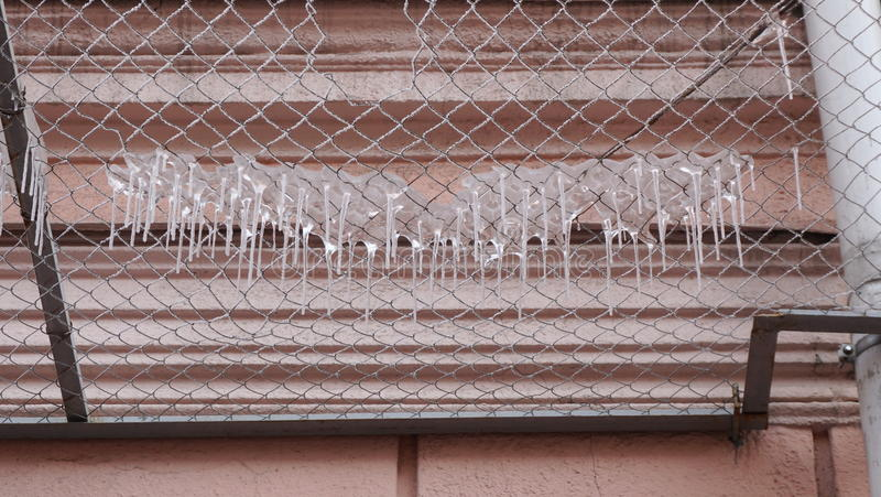 Viele Eiszapfen auf einem Sicherheitsgitter der Fassade des Gebäudes lizenzfreies stockbild