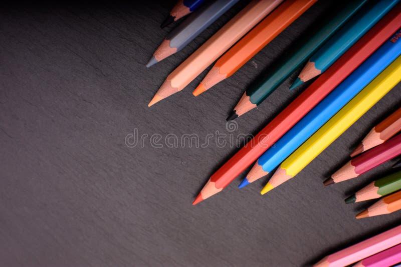 Viele farbigen Bleistifte auf einem schwarzen Steinschiefer, Platz für Text stockfotografie