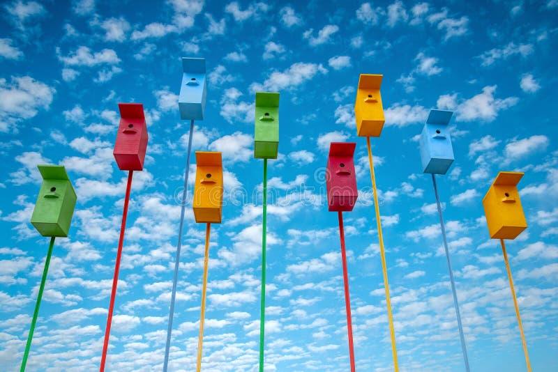Viele farbigen Vogelhäuser auf langen Stämmen im Himmelhintergrund lizenzfreie stockbilder