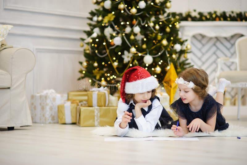 Viele Feiertagsverzierungen und -geschenke Kinder schreiben Santa Claus Briefe lizenzfreie stockbilder