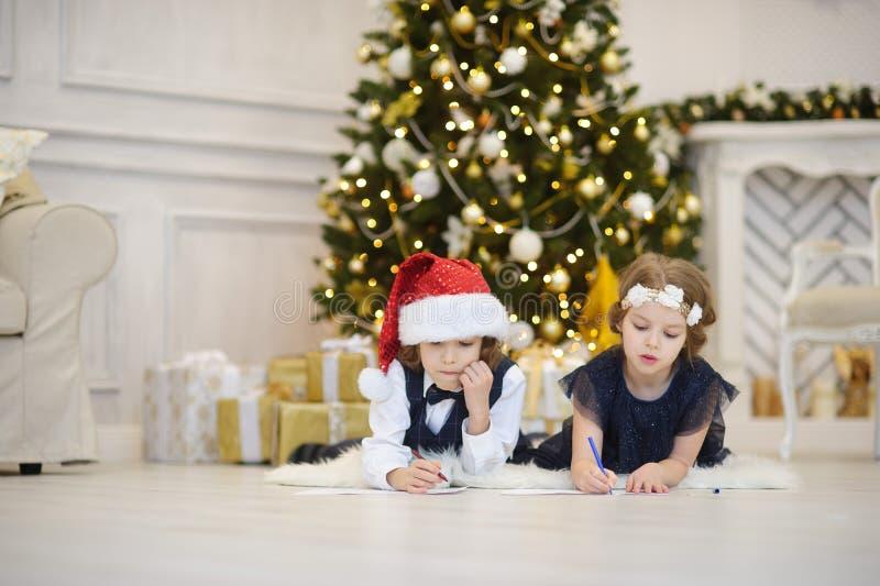 Viele Feiertagsverzierungen und -geschenke Kinder schreiben Santa Claus Briefe stockfoto