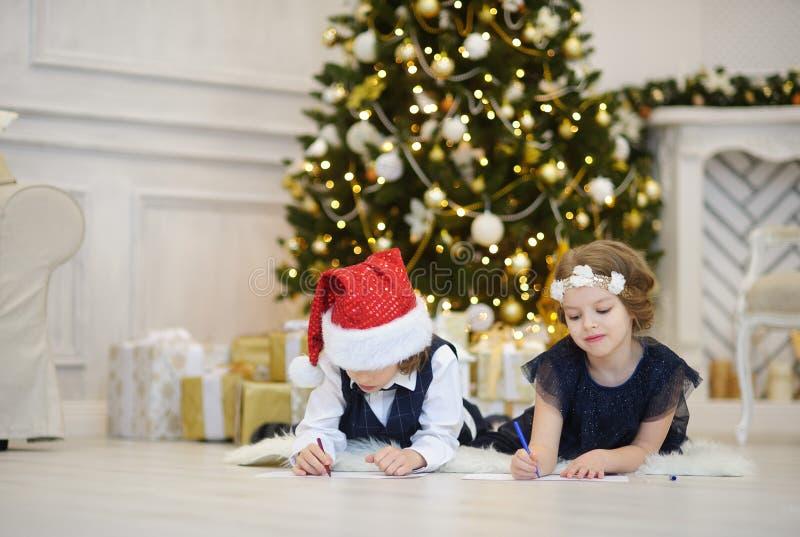 Viele Feiertagsverzierungen und -geschenke Kinder schreiben Santa Claus Briefe lizenzfreies stockbild