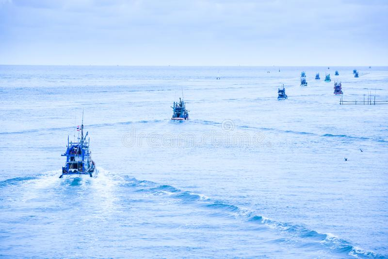 Viele Fischerboote, die heraus in das blaue Meer am Abend vorangehen stockfotos