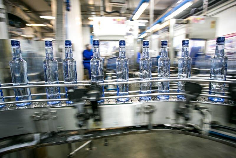 Viele Flaschen auf Förderband stockbilder