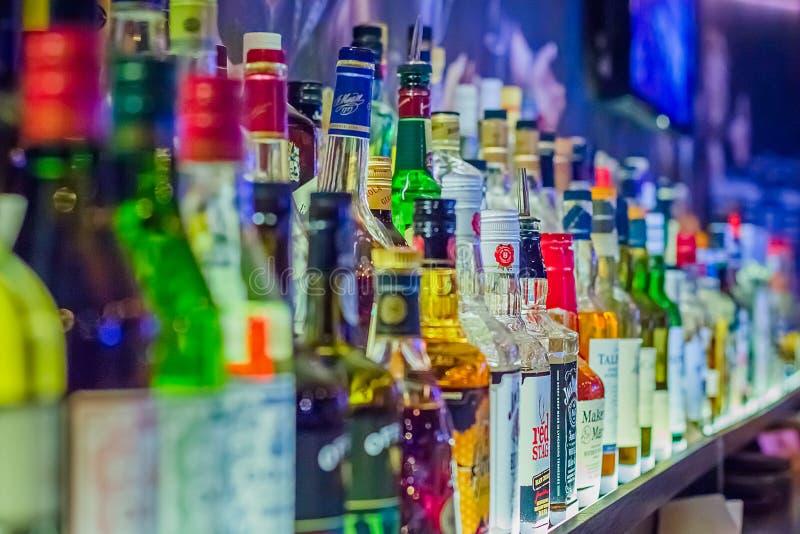 Viele Flaschen unterschiedlicher Alkohol durch Fässer lizenzfreie stockbilder