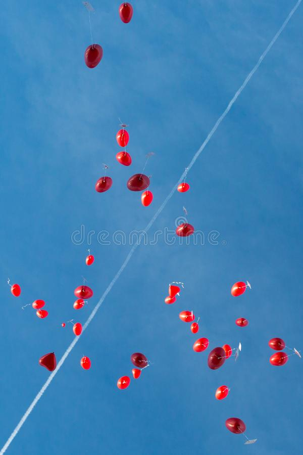 Viele fliegende rote Herz-förmige Ballone im blauen Himmel an der Hochzeit stockbilder