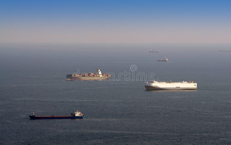 Viele Frachtschiffe, die auf Hafeneinfahrt warten lizenzfreies stockfoto