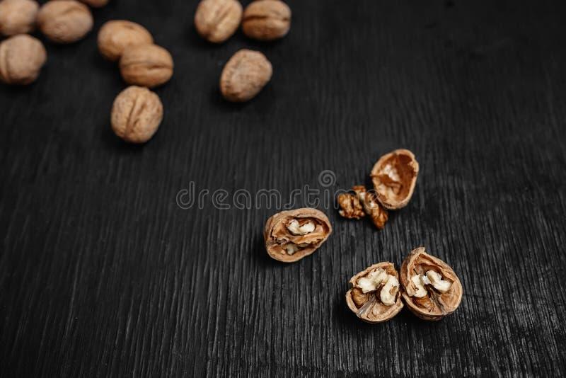 Viele frische Nüsse auf einem schwarzen hölzernen Hintergrund Optimale Verfahren für Designer stockfotografie