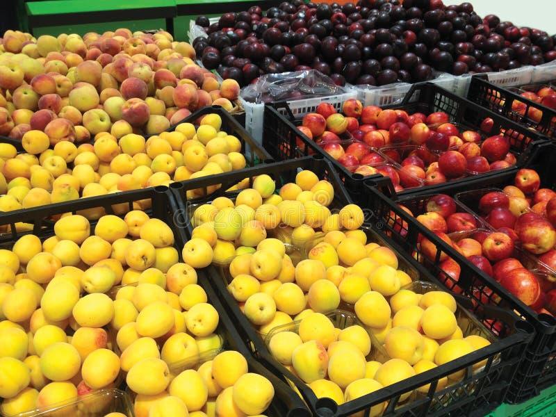 Viele Fruchtaprikosen, -pfirsiche, -nektarinen und -pflaumen, die im Kastensupermarkt liegen lizenzfreies stockfoto