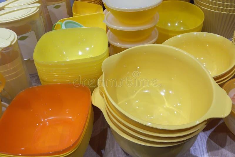 Viele gelben hellen Plastikschüsseln und Kastenküchengeschirr auf einer Tabelle stockbild