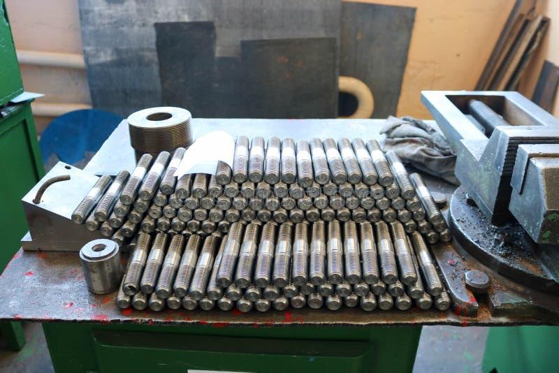 Viele glänzenden Metallbolzen mit auf dem Tisch in der Fabrik schnitzen, Nüssen, Eisenringen, Dichtungen, Metallverarbeitungswerk stockfotos