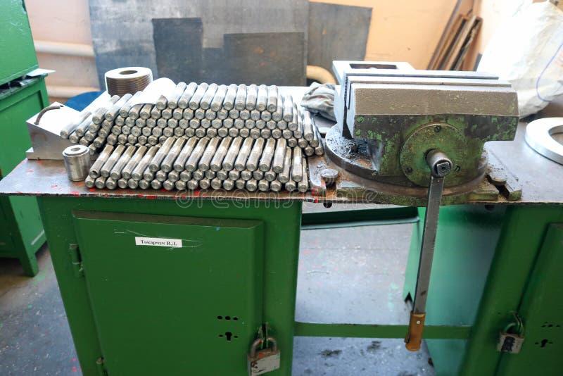 Viele glänzenden Metallbolzen mit auf der grünen Robotertabelle schnitzen, Nüssen, Eisenringen, Dichtungen, Metallverarbeitungswe stockbilder