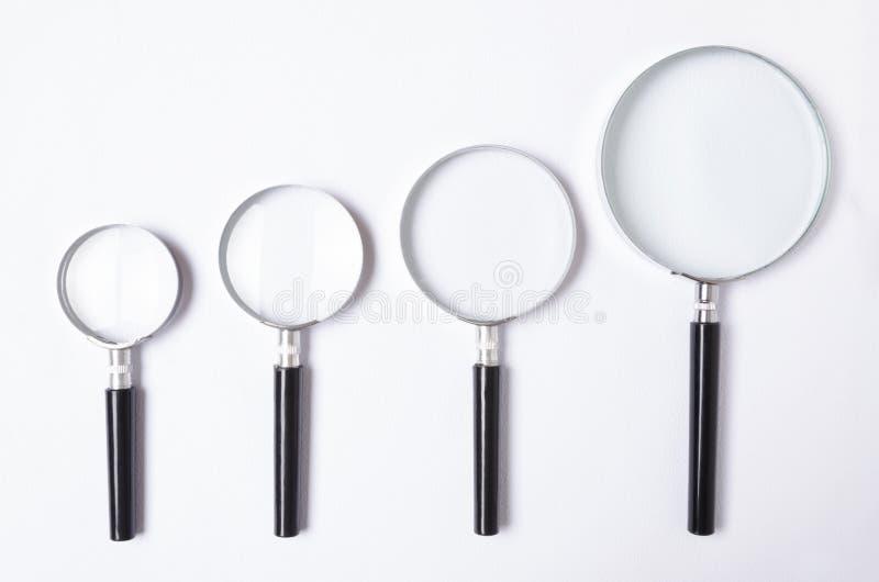 Viele Größen der Lupe auf weißer Tabelle, Draufsicht stockbild