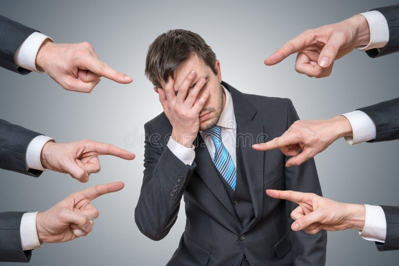 Viele Hände zeigen auf Mann und tadeln ihn lizenzfreie stockfotografie