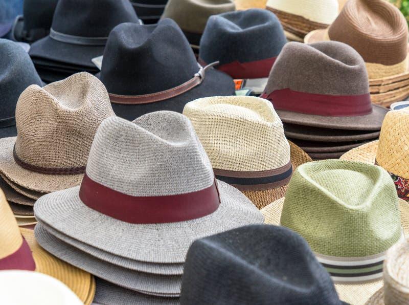 Viele Hüte für Männer in den verschiedenen Formen und in den Farben in einer Anzeige für Verkauf stockfotos