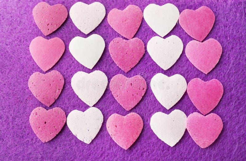 Viele Herzen auf purpurrotem Hintergrund lizenzfreie stockfotografie