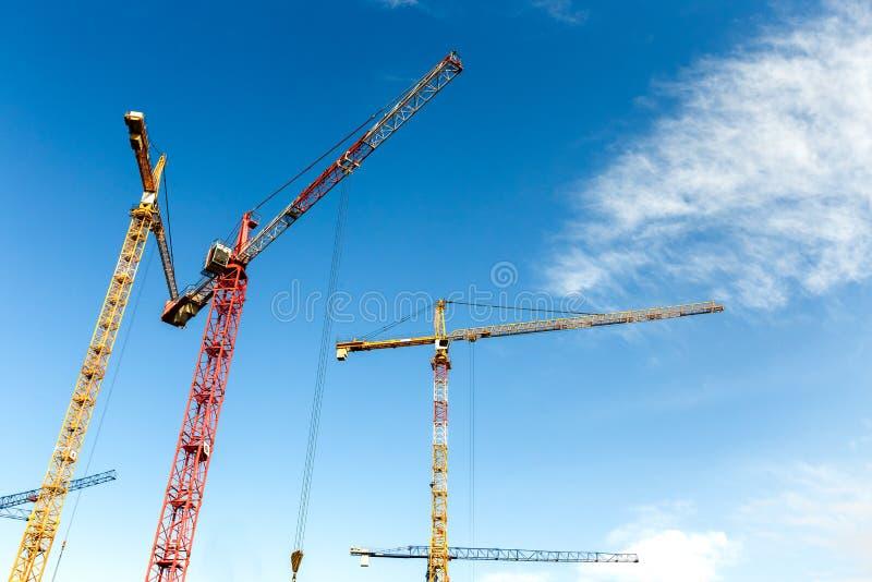 Viele hohen Turmkrane arbeiten an einem Bau von Neubauten stockbilder
