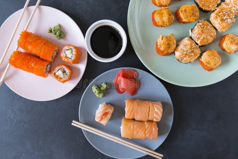 Viele japanischen Rollen mit Kaviar und Lachsen auf einer Platte, kalte japanische Rollen, gebackene heiße Rollen, Draufsicht, Ka stockfoto
