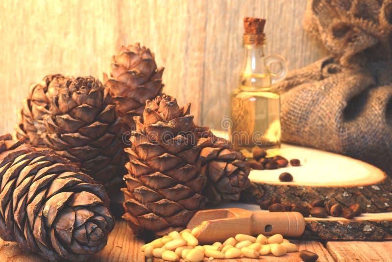 Viele Kiefernnüsse und Zedernkegel nahe bei einer Flasche Zeder ölen auf einer Tabelle in einer rustikalen Art stockbilder