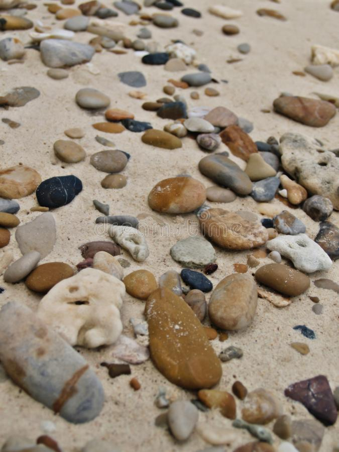 Viele Kiesfelsen zeichneten den Sand auf dem Strand lizenzfreies stockfoto
