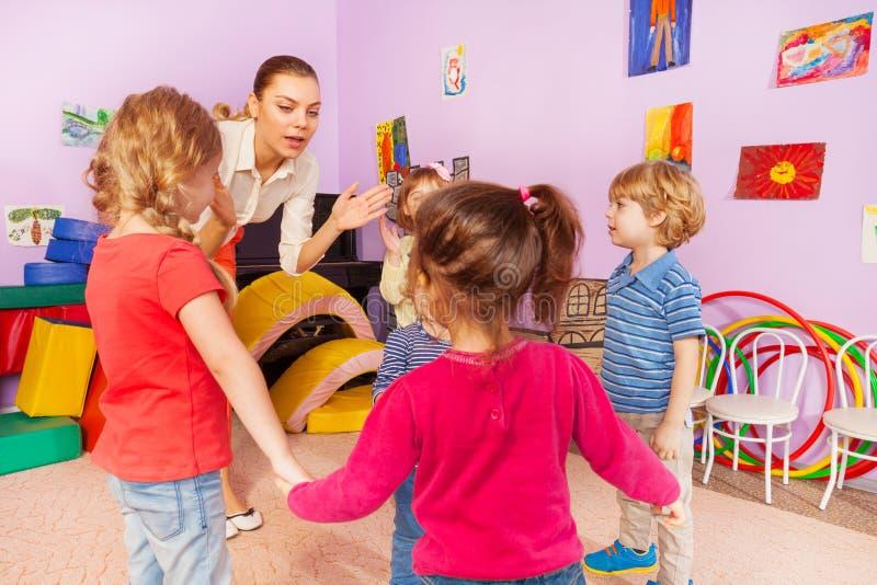 Viele Kinder klatschen Hände mit Lehrer im Kindergarten lizenzfreies stockfoto