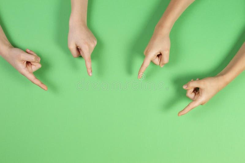 Viele Kinderhände, die auf etwas auf hellgrünem Hintergrund zeigen lizenzfreies stockbild