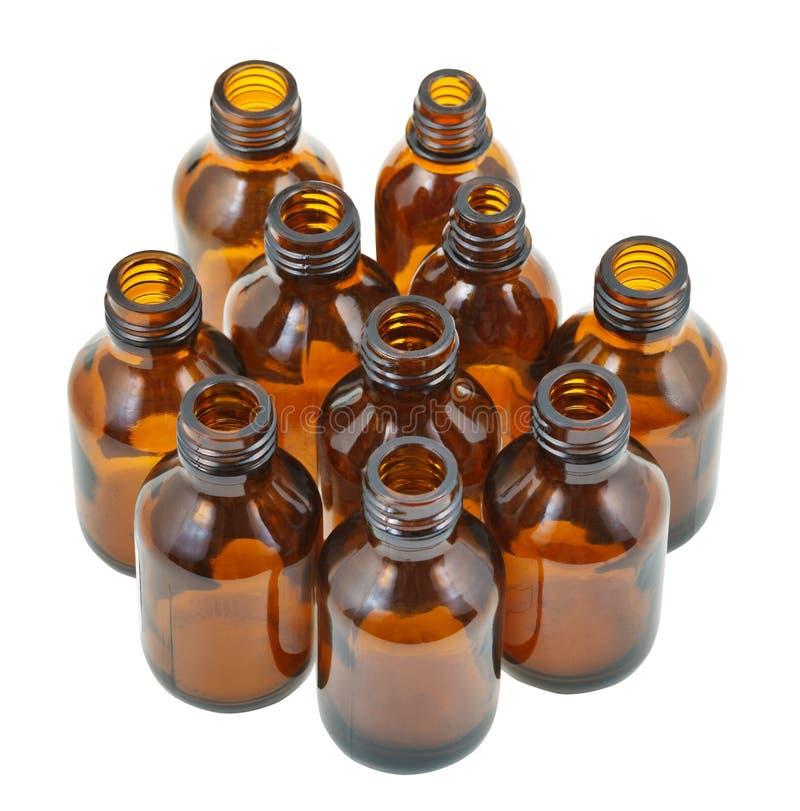 Viele kleinen offenen braunen ovalen Apothekenglasflaschen lizenzfreie stockbilder