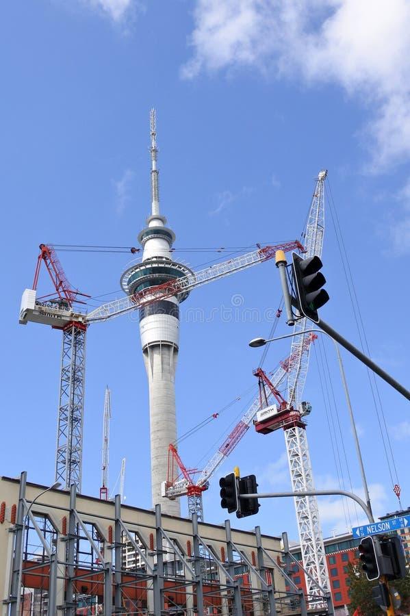 Viele Kräne gegen Auckland-Himmelturm lizenzfreie stockfotografie