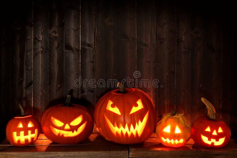 Viele Laternen Halloweens Jack O nachts gegen dunkles Holz lizenzfreies stockfoto