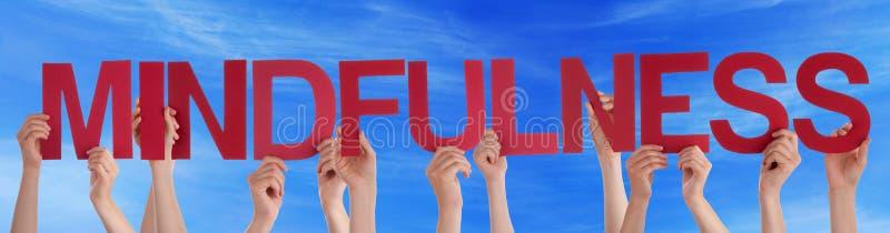 Viele Leute-Hände, die roter gerader Wort Mindfulness-blauen Himmel halten stockfotografie