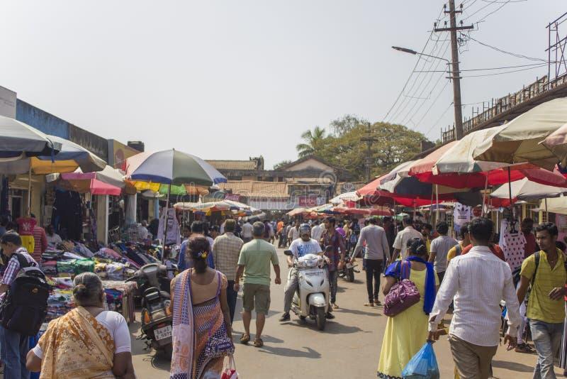 Viele Leute im indischen Markt der Straße zwischen den Geschäften unter Regenschirmen stockfoto