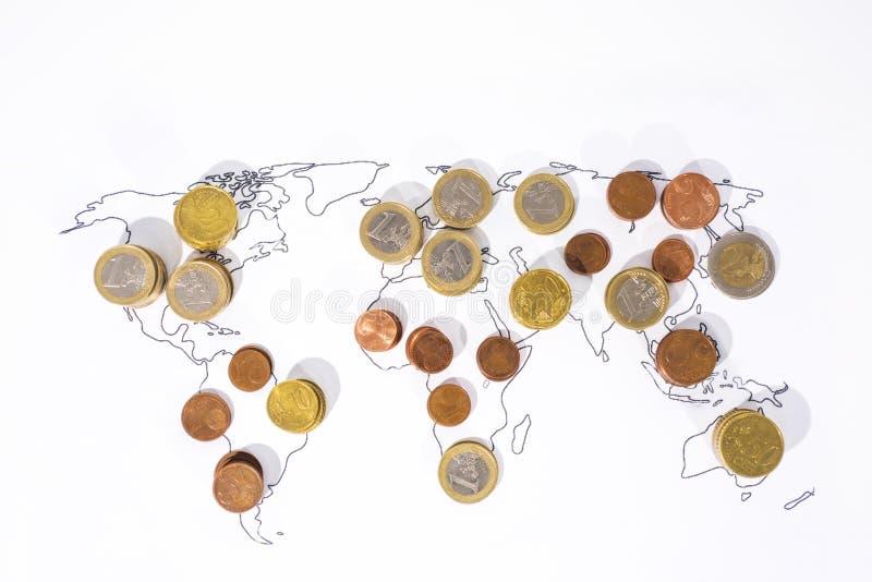 Viele Münzen auf Weltkarte lizenzfreie stockbilder