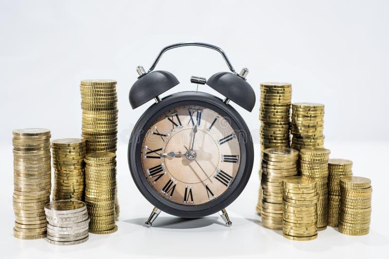 Viele Münzen mit eleganter schwarzer Uhr lizenzfreies stockbild