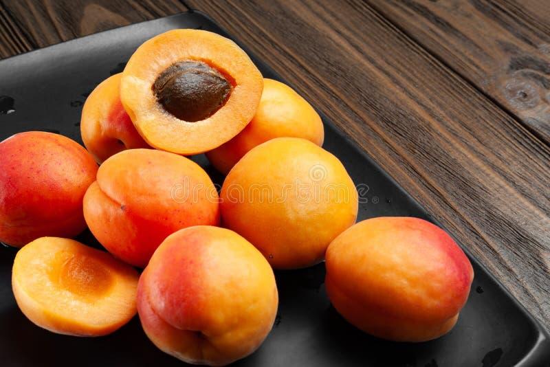 Viele nass Aprikosen auf einem nass dunklen Hintergrund Frische saftige rötliche Aprikosen auf einer dunklen Lehmplatte gespritzt lizenzfreies stockbild