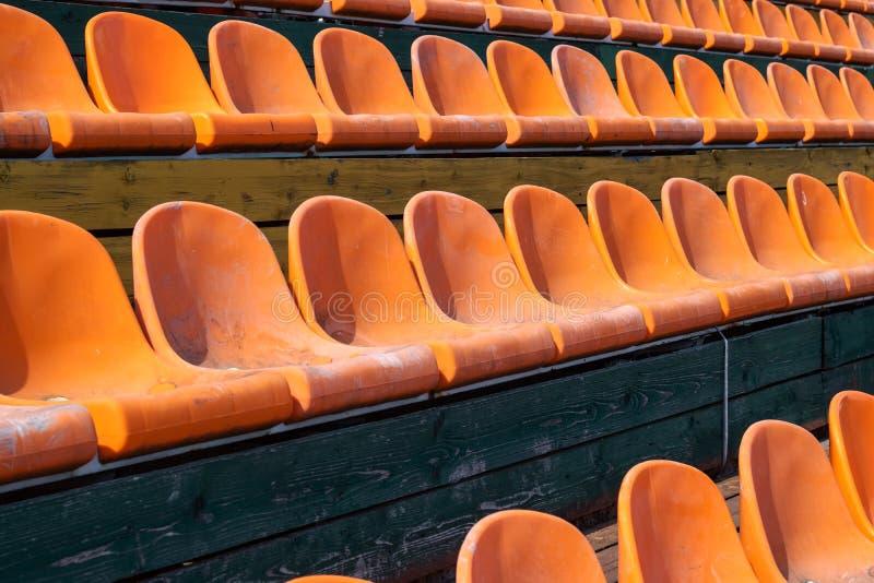 Viele orange Plastiksitze nah oben, Hintergrund stockbild