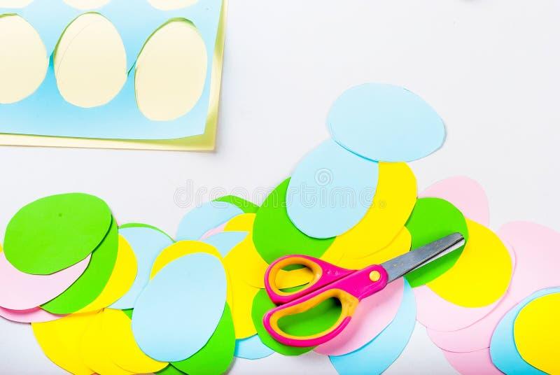 Viele Ostern-Papiereier, -scheren und -blätter des farbigen Papiers lizenzfreie stockfotos