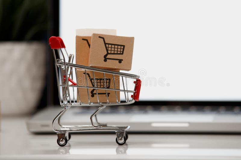 Viele Papierkästen in einem kleinen Einkaufswagen auf einer Laptoptastatur Konzepte über das on-line-Einkaufen, dass Verbraucher  stockbild