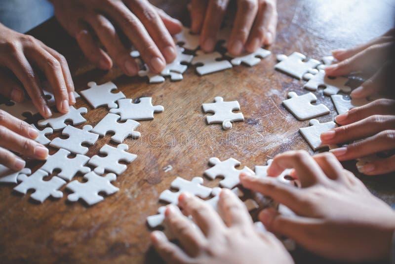 Viele Personen, die Stücke des Puzzlen, des Teamwork-Konzeptes, der Geschäftsverbindung, des Erfolgs und des Strategiekonzeptes,  lizenzfreies stockbild