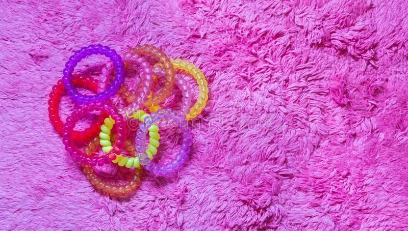 Viele Plastikhaarkabelgummibänder in den verschiedenen Farben lokalisiert auf einem weichen rosa Hintergrund stockfoto