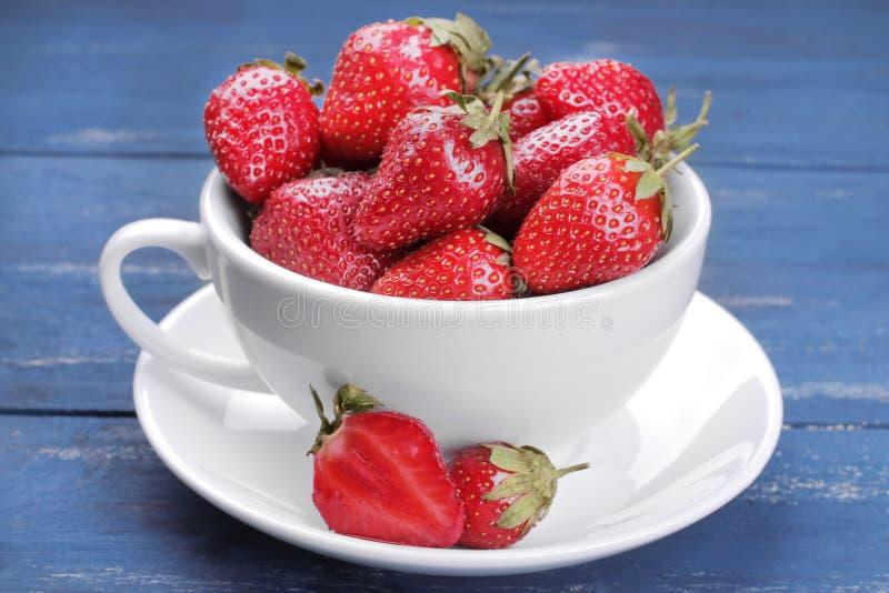 Viele reifen, frischen Erdbeeren in einer Schale auf einem blauen hölzernen Hintergrund stockfotografie