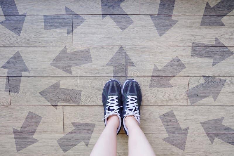 Viele Richtungs-Pfeil-Wahlen Selfie von Laufschuhen mit gezogenen Pfeilen Frau Violet Sneakers mit Entscheidungen über Bretterbod lizenzfreie stockfotografie
