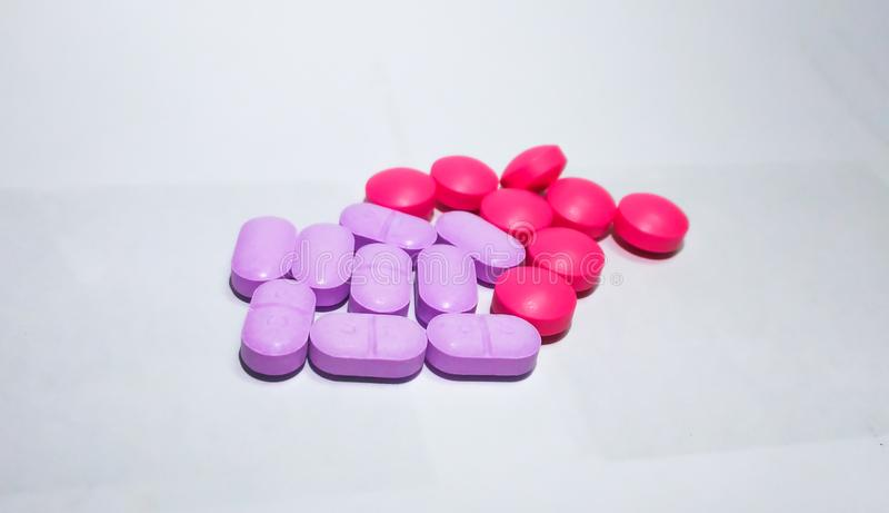 Viele rosa und purpurroten Pillen legen auf einen weißen Hintergrund lizenzfreie stockfotos