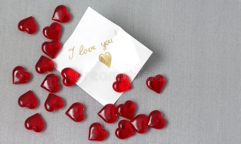 Viele rote transparente Herzen mit einem Anmerkung ich liebe dich Valentinsgruß ` s Tag stockbild